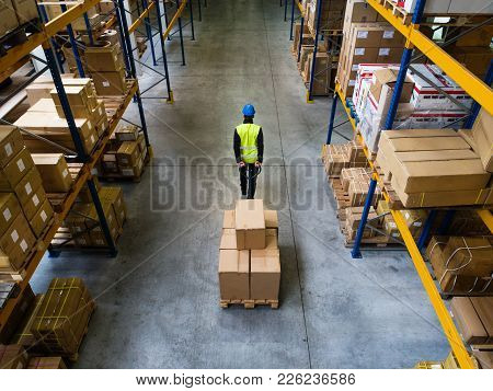 Young Male Warehouse Worker Pulling A Pallet Truck With Boxes. Rear And High Angle View.