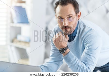 Woking. Attractive Concentrated Dark-haired Bearded Man Wearing Glasses And Working On His Laptop Wh