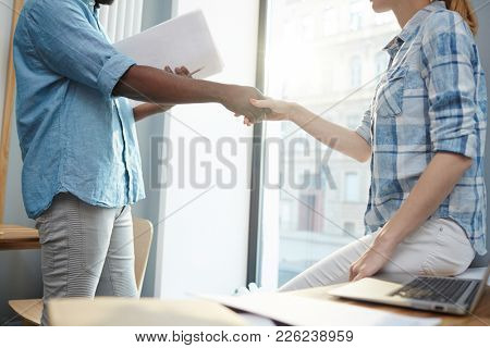 Intercultural business partners handshaking after signing new contract in office