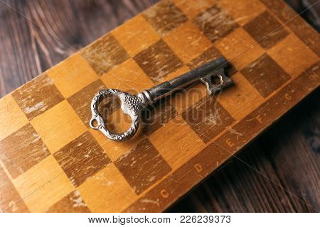 Vintage Key On An Old Chessboard, View From Above
