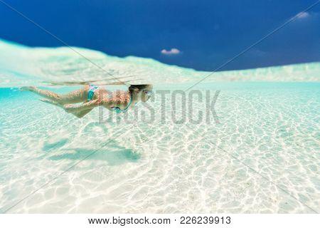 Split underwater photo of a little girl swimming in tropical ocean