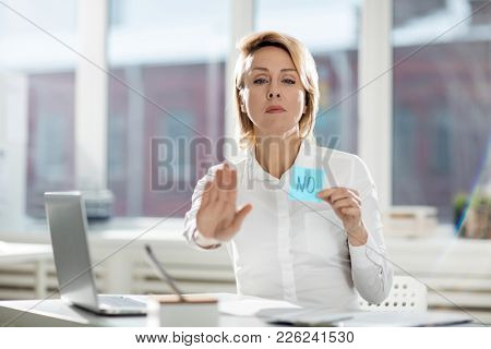 Serious businesswoman stopping someone by gesture and negation sticker