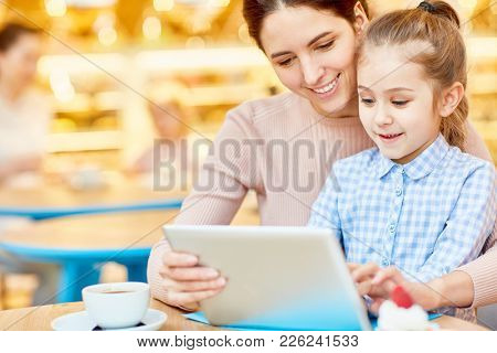 Happy young woman and her daughter sitting in cafe with tablet and having fun while searching in the net