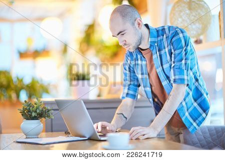 Young man in casualwear leaning over table while networking at home