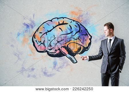 Handsome Caucasian Businessman Drawing Creative Brain Sketch On Concrete Wall Background. Brain Stor