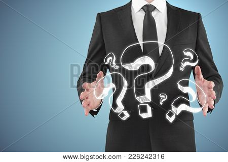 Businessman Holding Question Marks On Blue Background. Confusion And Faq Concept