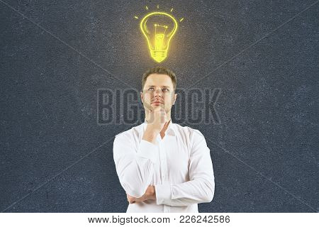 Thoughtful Handsome Man With Draw Lamp Standing On Concrete Wall Background With Copy Space. Success
