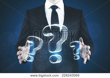 Businessman Holding Abstract Drawn Question Marks On Blue Background. Faq And Confusion Concept