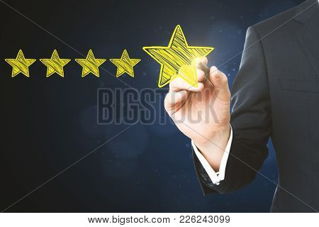 Businessman Pointing At Abstract Stars On Blurry Blue Background. Experience Rating And Ranking Conc
