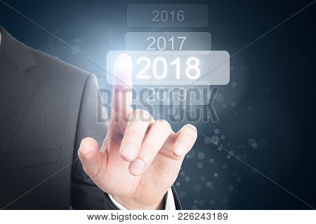 Businessman Pointing At Glowing Digital 2018 Touchscreen. Future And Innovation Background