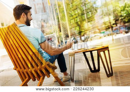 Relaxing Person. Cheerful Calm Relaxed Man Having A Good Time While Resting In A Cute Cafe With A Mo