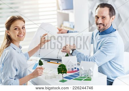 Happy Co-workers. Good-looking Exuberant Bearded Man Smiling And Holding A Drawing And Working With