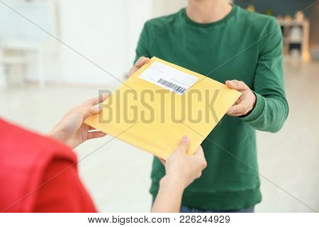 Man receiving parcel from courier indoors