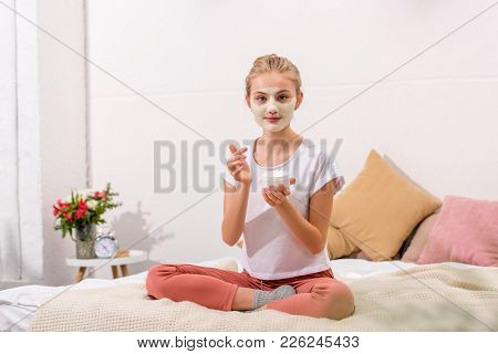 Young Woman Applying Clay Mask On Face While Sitting On Bed At Home