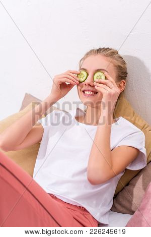 Happy Young Woman Applying Cucumber Slices On Eyes At Home