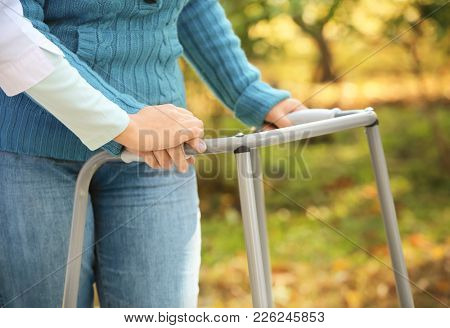Senior woman with walking frame and young caregiver, closeup