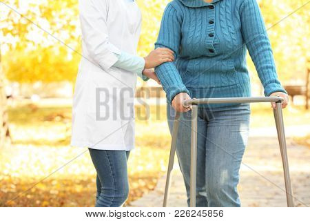 Senior woman with walking frame and young caregiver in park