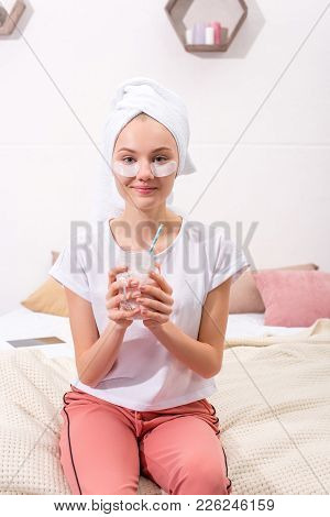 Attractive Young Woman With Cosmetic Facial Patches With Glass Of Milkshake At Home