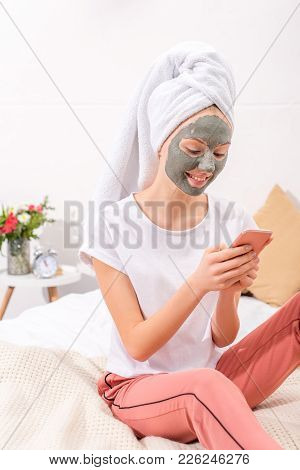Young Woman With Cosmetic Clay Mask Using Smartphone At Home