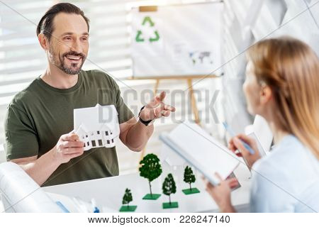 Discussing Work. Attractive Cheerful Bearded Man Smiling And Holding A House Miniature While Working