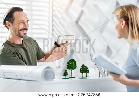 Discussing Project. Attractive Exuberant Bearded Man Smiling And Holding A House Miniature While Wor