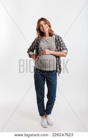 Happy Pregnant Woman With Hands On Tummy Isolated On Grey