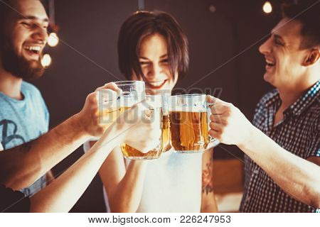 Friends Toasting With Glasses Of Light Beer At The Pub. Beautiful Background Of The Oktoberfest. A G