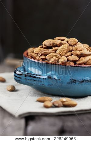 Whole Almonds In Bowl Over A Wooden Table Against A Rustic Background.