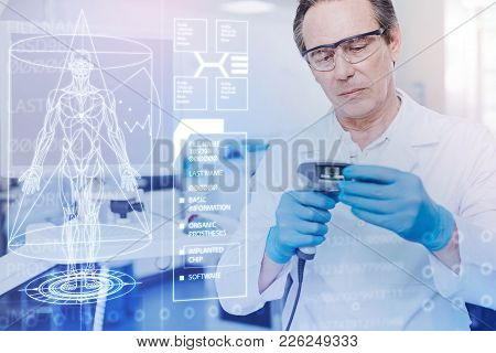 Very Careful. Calm Clever Experienced Doctor Feeling Concentrated While Standing With A New Tool In