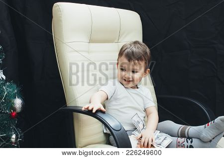 Child On A Chair Filled Up With Money, Dollars And Rubles