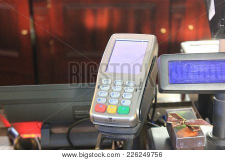 Payment Machine For Bank Credit Cards In Retail Store Desk Close Up. Small Payment Terminal At Cashi