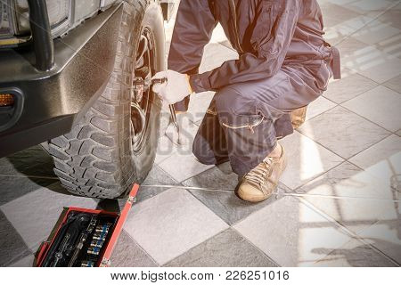 Car Repair Workers Wearing Dark Blue Uniforms Are Using Tools To Remove The Wheel Nuts To Check And