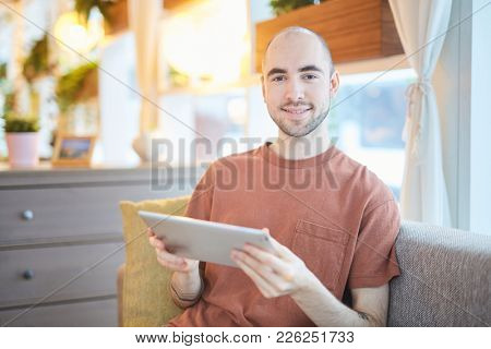 Young attractive man in t-shirt relaxing in cafe or at home with tablet