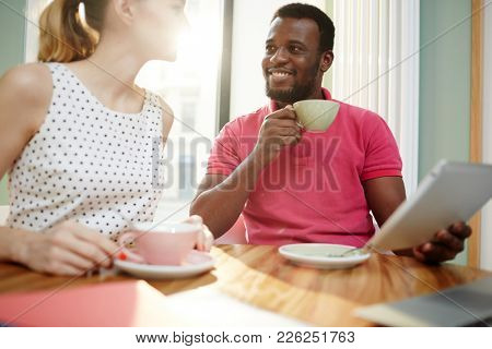 Contemporary manager with gadget talking to colleague during coffee break in office
