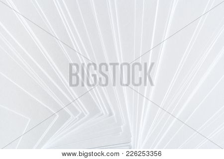 White Geometric Background From A Lot Of Clean Paper Sheets Laid Out Carelessly As Fan.