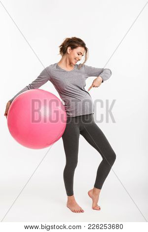Smiling Pregnant Woman Holding Fit Ball And Pointing At Belly Isolated On White
