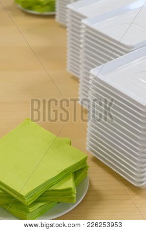 A Stack Of Plastic Plates And Napkins On A Table