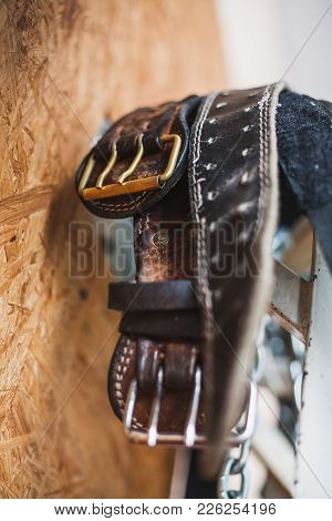 A Bunch Of Old Worn Leather Weightlifting Belts Hanging Near A Wooden Panel Wall, Shallow Depth Of F