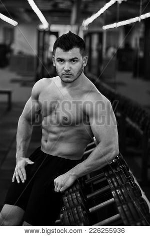 Muscular bodybuilder in gym take dumbbell from dumbbell rack.Strong athletic man naked torso working