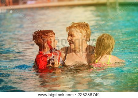 Grandmother With Kids Swim Have Fun In Pool, Active Retirement