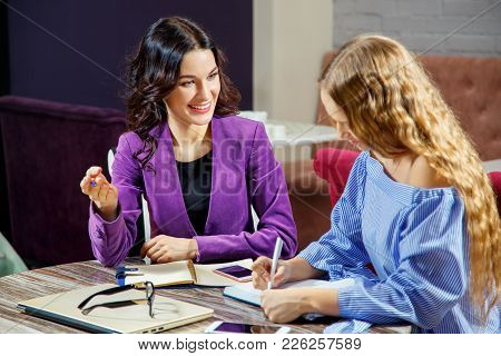 The Teacher Explains To The Student New Topic. A Student Takes Notes In A Notebook. Individual Train