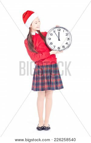Isolated Portrait Of Girl Wearing School Uniform And Santa Hat Holding Clock Showing Five Minutes To