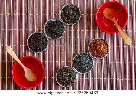 Ivan Tea, Rooibos Marrakech, Black Tea, Green Tea And Wooden Spoons In Red Bowls On A Brown Bamboo M