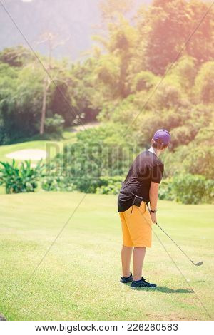 Golfer hitting golf shot with club on course while on summer vacation,boy playing golf on a golf cou