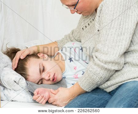 A Child Being Cared For During An Epileptic Seizure By A Qualified Special Needs Carer