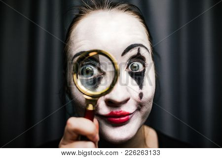 A Girl In The Image Of A Mime Holds A Magnifier. Comic Actor
