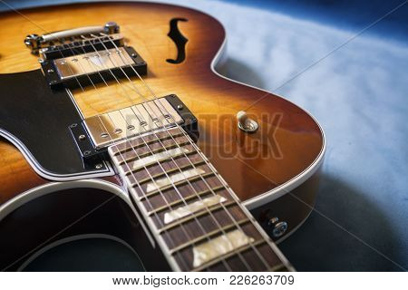Acoustic Guitar Close Up In Blue Background