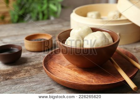Bowl with tasty baozi dumplings on table