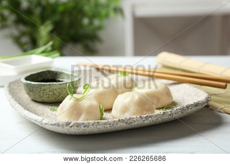 Plate with tasty baozi dumplings and soy sauce on table