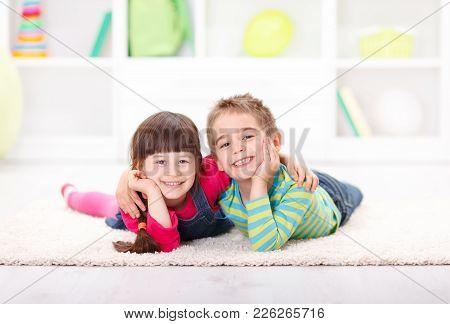 Happy Little Boy And Girl Lying On The Floor